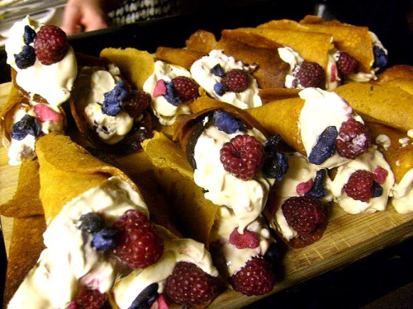 brandy snaps filled with cream and marscarpone with crystallized violets and raspberries